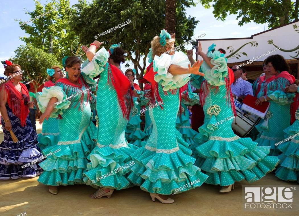 Stock Photo: Women wearing beautifully coloured gypsy dresses perform traditional Andalusian dances at the Feria del Caballo (Horse Fair) in Jerez de la Frontera.