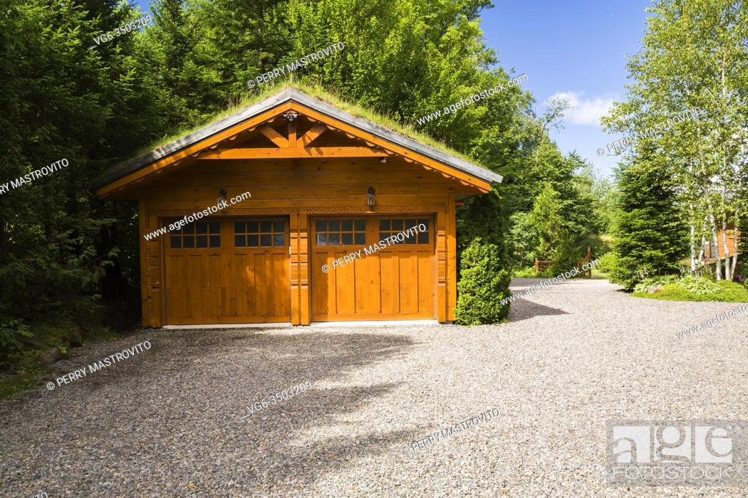 Stock Photo: Golden-brown stained piece sur piece Eastern white pine log and timber 2 car garage with carved wood details and Gramineae or Poaceae - Grass and Bryophyta -.