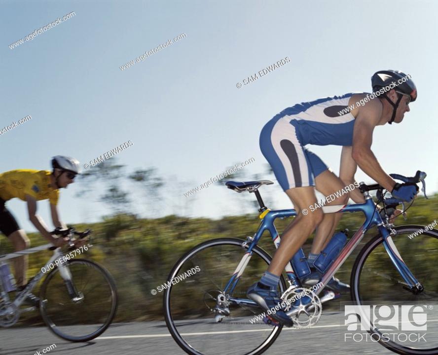 Stock Photo: Two men racing on bikes.