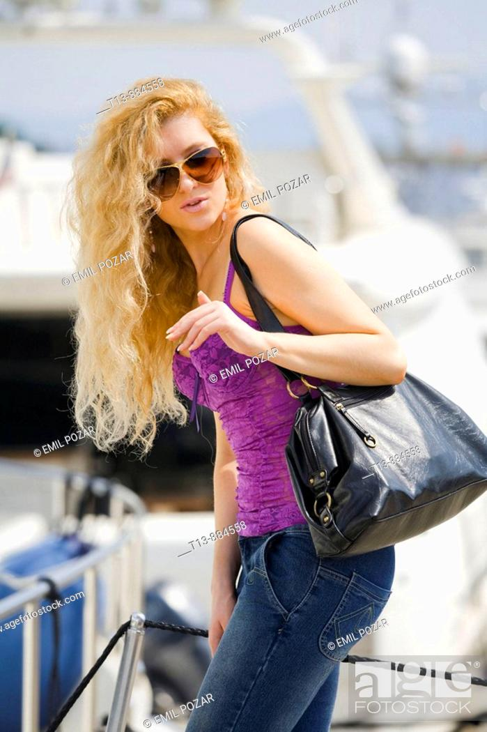 Stock Photo: Attractive young woman with spectacles and big purse is boarding a yacht.