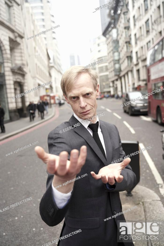 Stock Photo: preternatural businessman with open hand palms at street in city of London, UK.