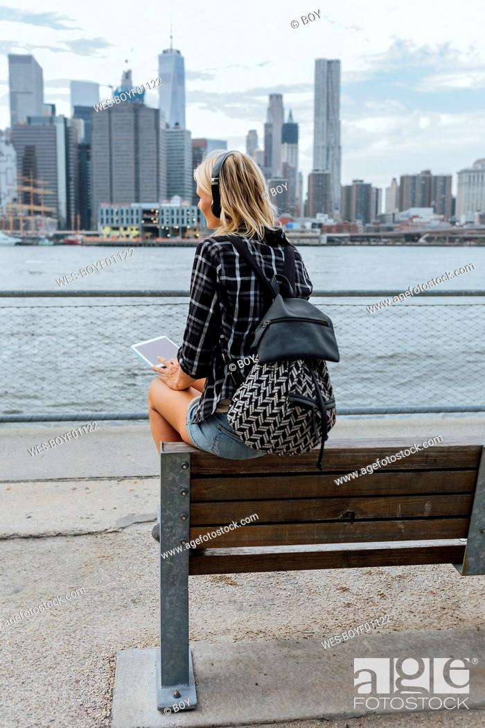 Stock Photo: USA, New York City, Brooklyn, young woman sitting at the waterfront with backpack, headphones and tablet.
