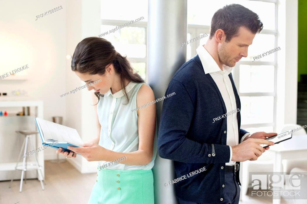 Stock Photo: Man using an electronic book with a woman reading a book.