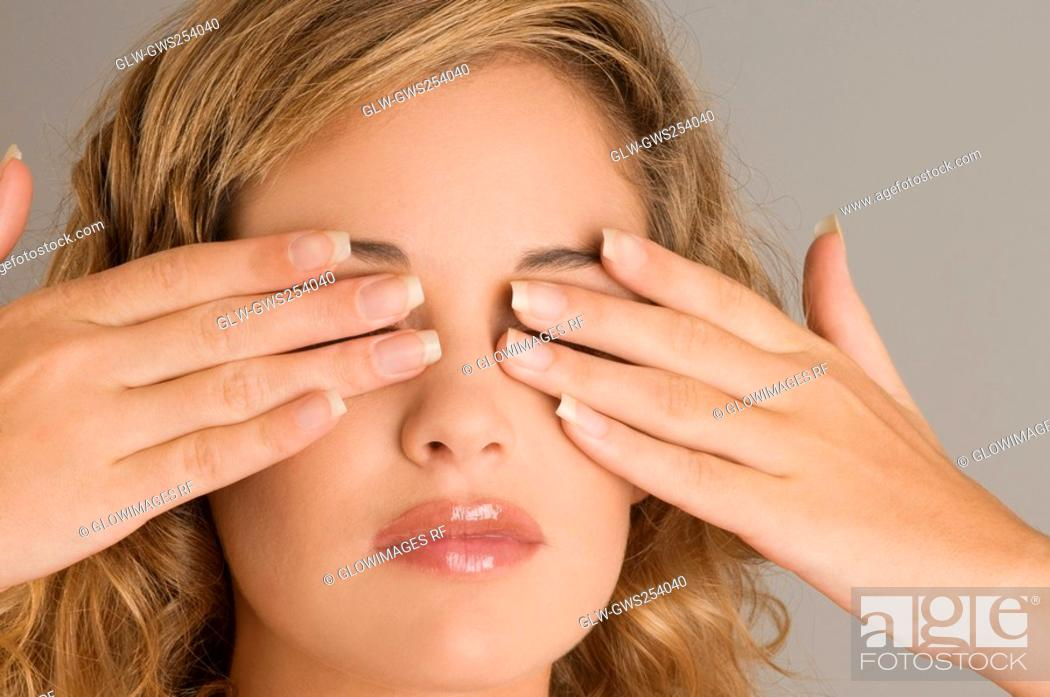 Imagen: Close-up of a young woman covering her eyes with her hands.