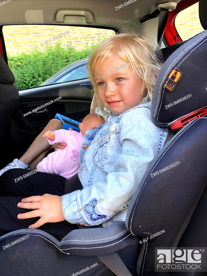Stock Photo: Tree years old girl sit in a safety car seat.