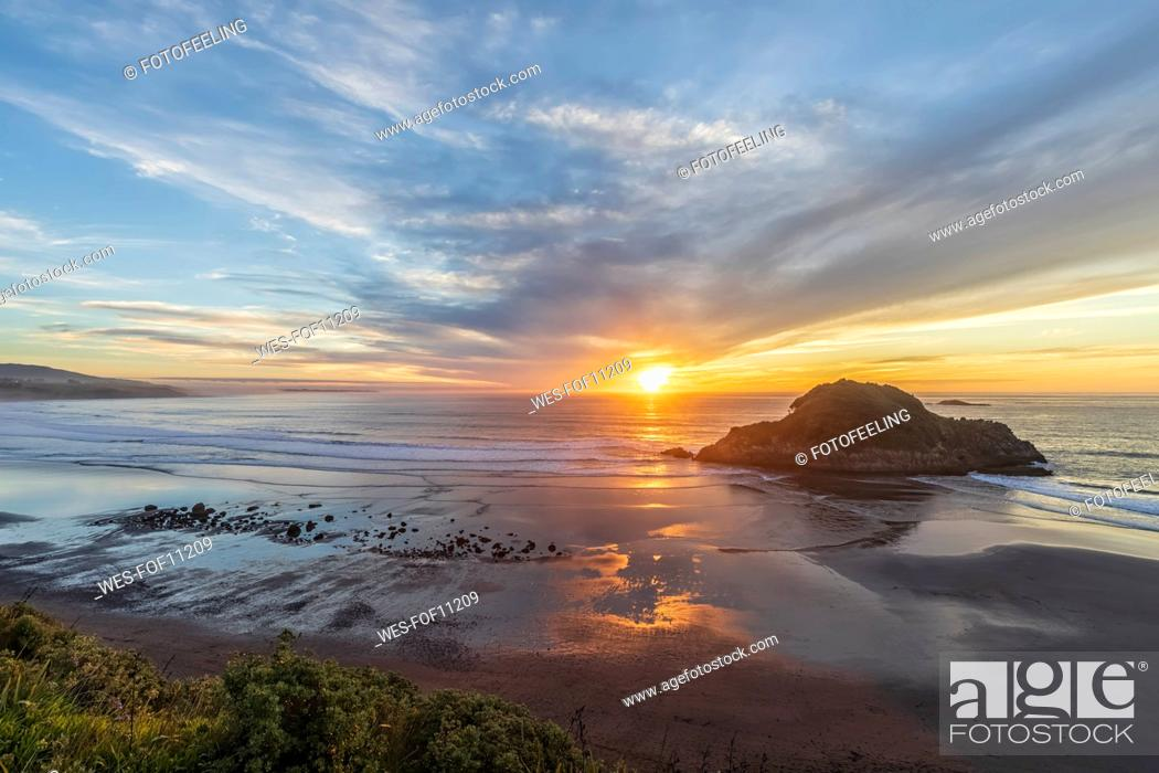 Stock Photo: New Zealand, Tongaporutu, Clouds over sandy coastal beach at sunset with Motuotamatea island in background.