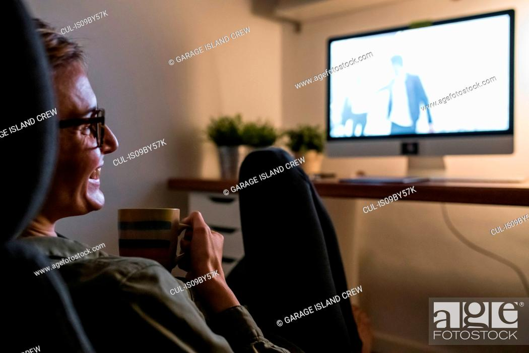 Stock Photo: Woman relaxing in front of TV with mug of warm drink.