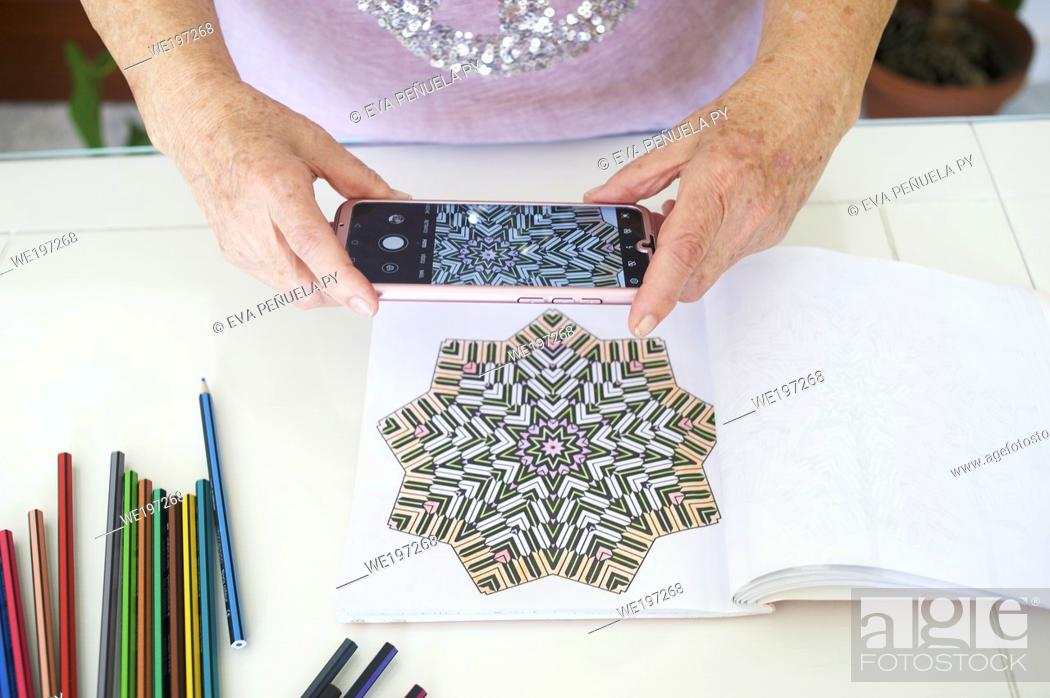 Stock Photo: mature woman coloring her sketchbooks in the living room of her house in Seville (Spain).