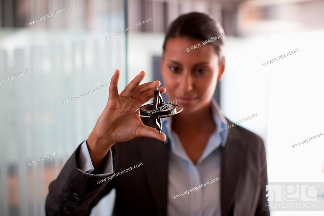 Stock Photo: Businesswoman holding gyroscope in office.