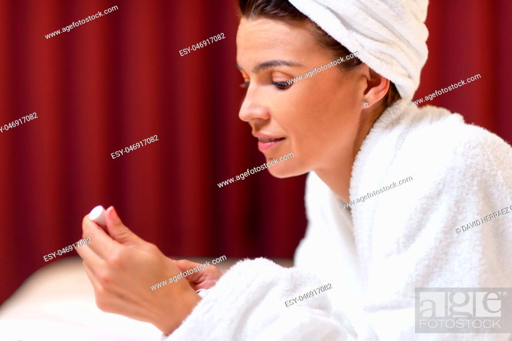 Imagen: Beautiful woman in bathrobe with a towel in her head applying lipstick.