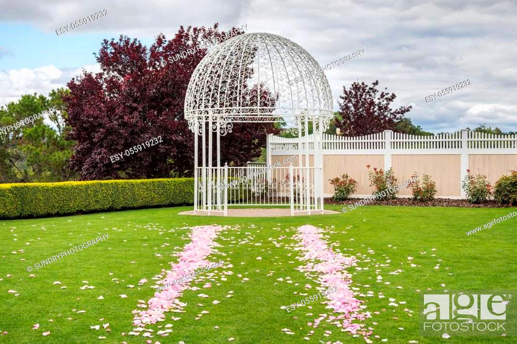 Stock Photo: Outdoors wedding venue with forged iron wedding arch and rose petals spread on a green grass lawn; cloudy sky background.