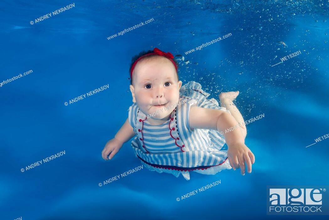 Stock Photo: A little girl in a dress floats under waterin a swimming pool.