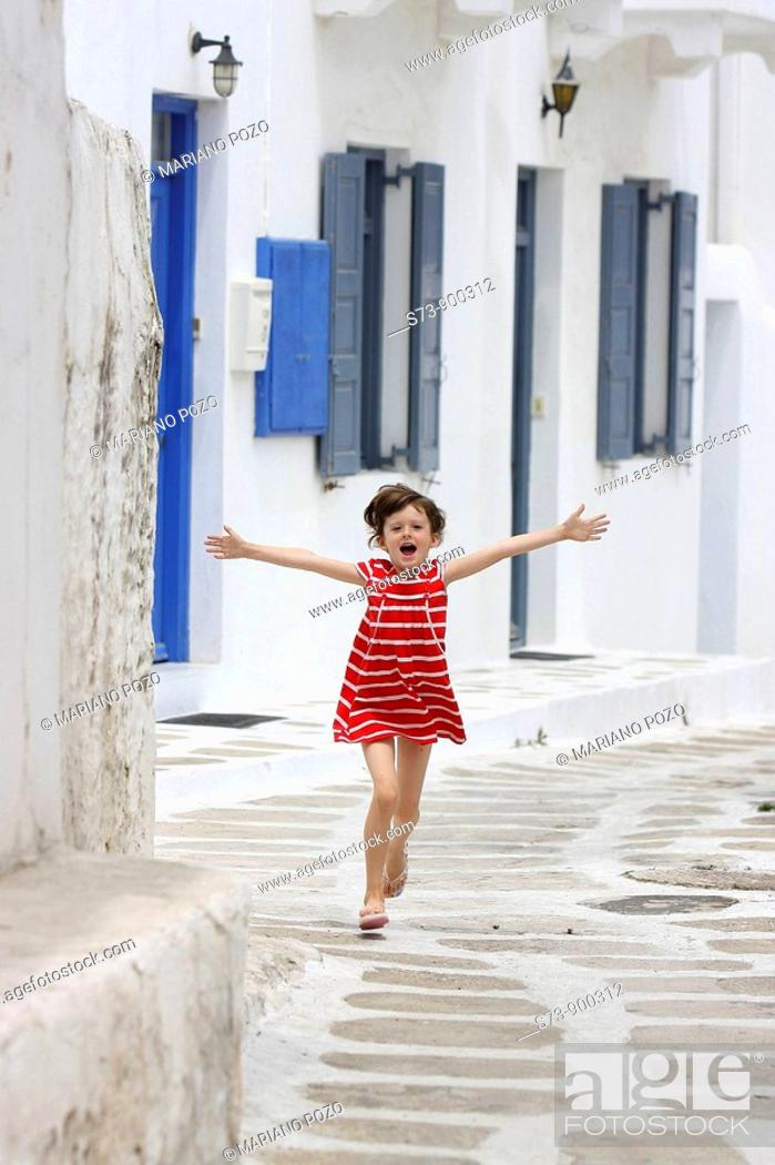 Stock Photo: 6 years old girl running in a Mykonos street, Cyclades islands, Greece, Europe.