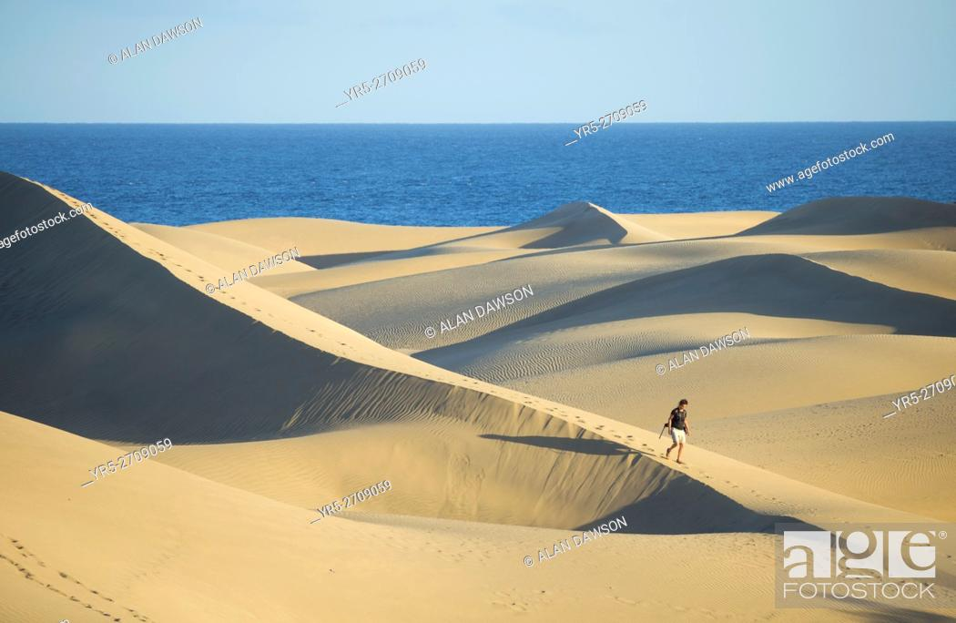 Stock Photo: Female hiker with backpack walking through the vast expanse of sand dunes at Maspalomas, Gran Canaria, Canary Islands, Spain, Europe. Model released.