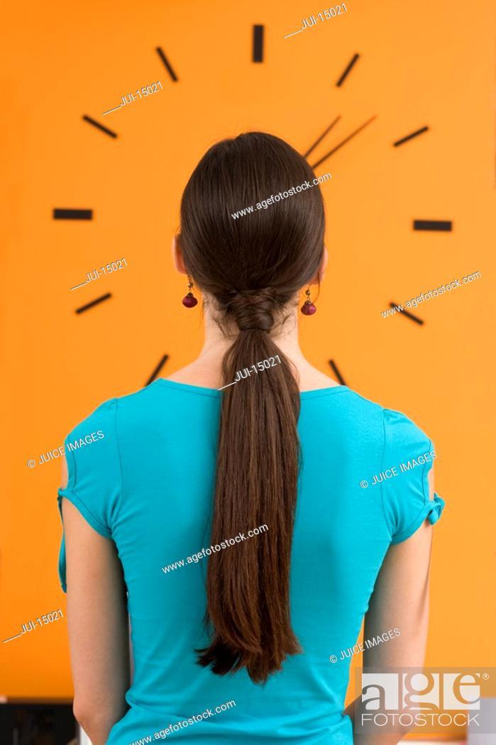 Stock Photo: Woman looking at wall clock, rear view.