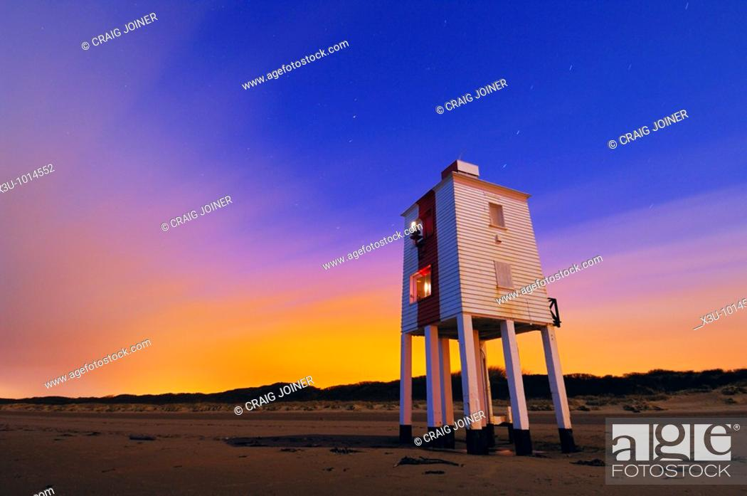 Stock Photo: The wooden lighthouse at Burnham-on-Sea at night  The cloud in the sky is illuminated from light pollution of nearby sodium street lamps  The lighthouse.