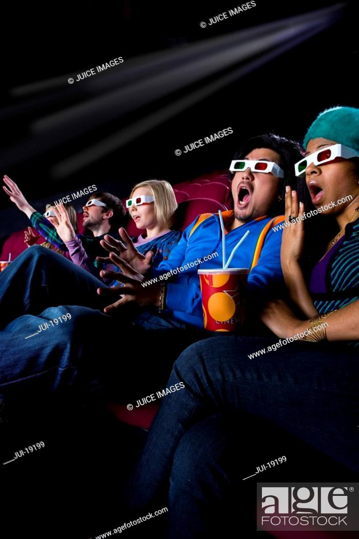 Stock Photo: Audience in cinema wearing 3D glasses, making faces, low angle view.