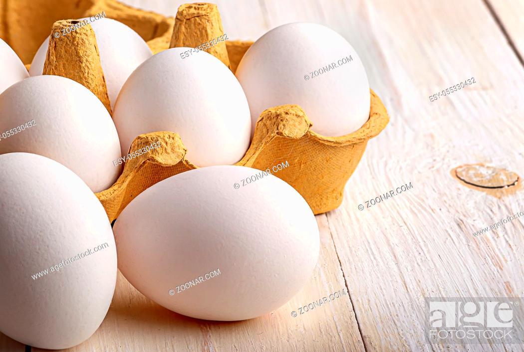 Stock Photo: White eggs near paper tray on white table closeup.