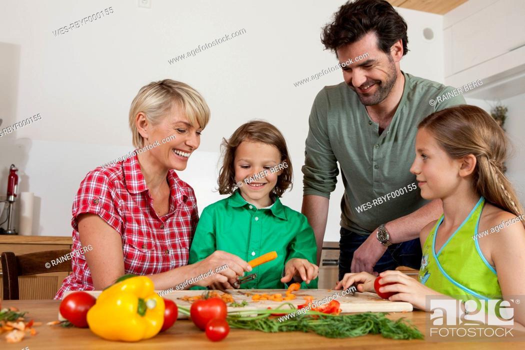 Stock Photo: Germany, Bavaria, Nuremberg, Family cutting vegetables.