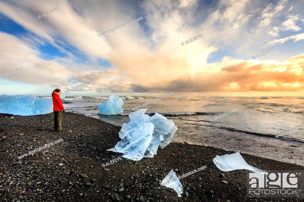Stock Photo: Tourist standing among ice pieces on a beach in southern Iceland.
