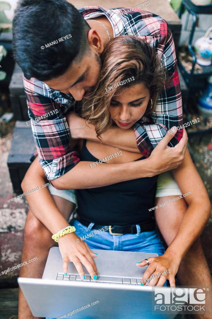 Stock Photo: Young couple sitting embraced in the steps of their wooden house with a laptop.
