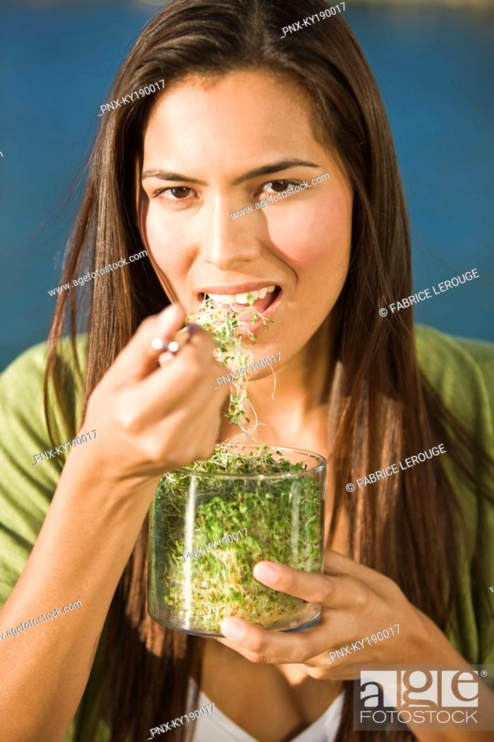 Stock Photo: Portrait of a woman eating bean sprouts.