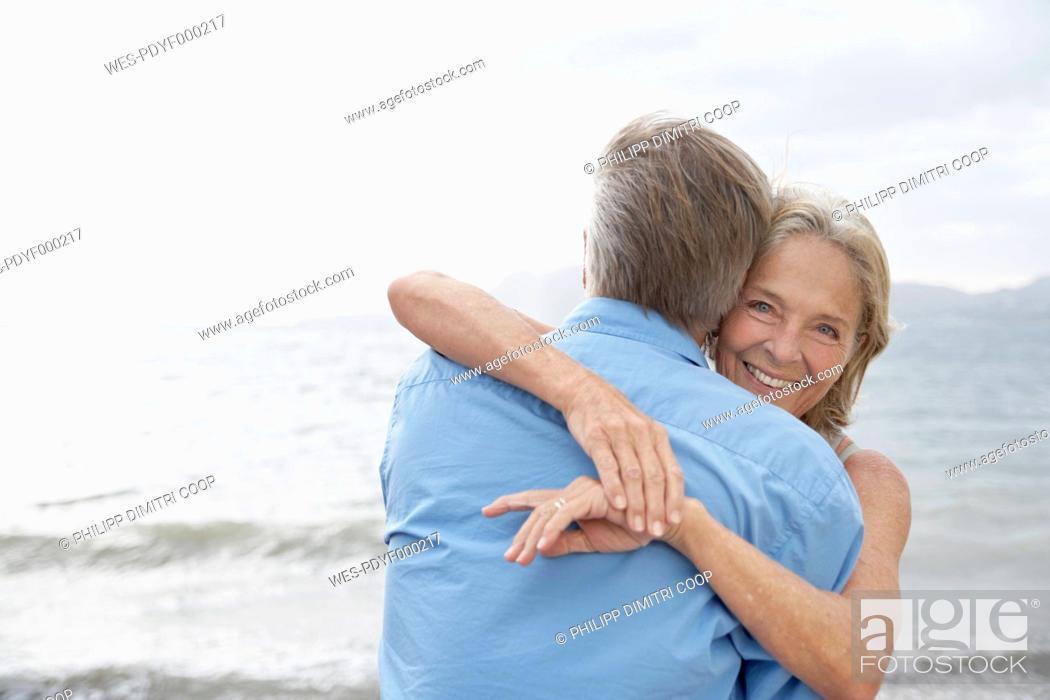 Stock Photo: Spain, Mallorca, Senior couple embracing on beach.