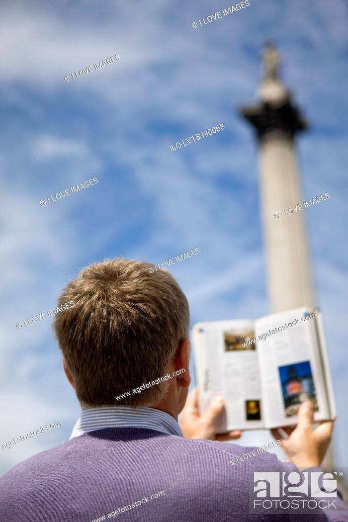 Stock Photo: A middle-aged man in front of Nelson's column, looking at a guidebook.