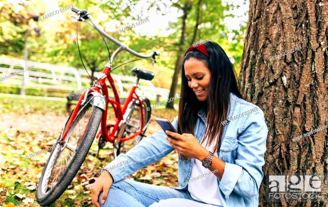 Stock Photo: Smiling young woman looking on cell phone in a park in autumn.