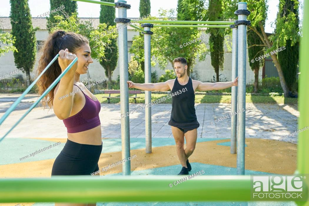 Stock Photo: Young woman and man practicing calisthenics in a park on sunny day.