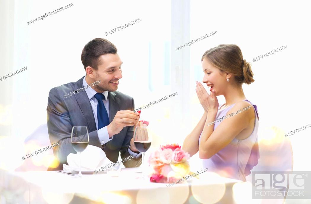 Stock Photo: restaurant, couple and holiday concept - smiling man proposing to his girlfriend at restaurant.
