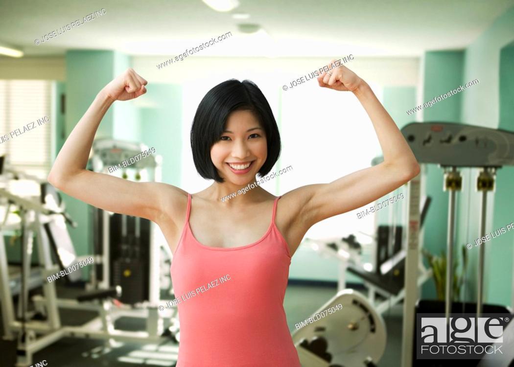 Stock Photo: Filipino woman flexing biceps in health club.