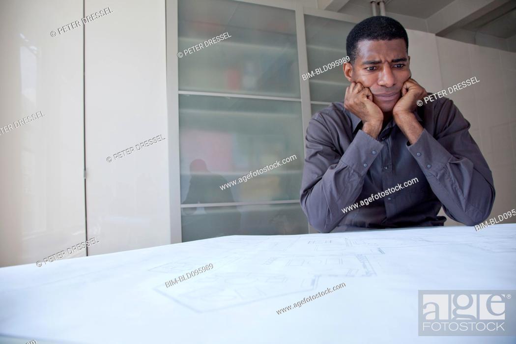 Stock Photo: Black businessman reviewing blueprints.