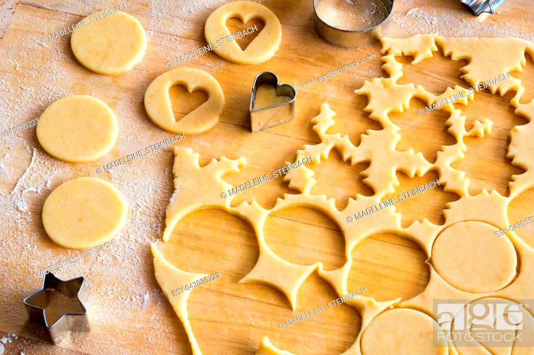 Stock Photo: Preparation of traditional Linzer Christmas cookies - cutting out star and heart shapes from rolled out dough.