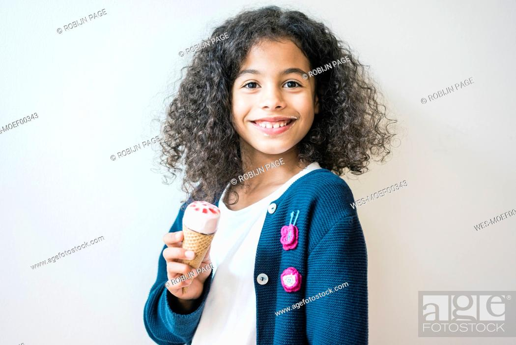 Imagen: Cheeky little girl smiling at camera, eating ice cream.