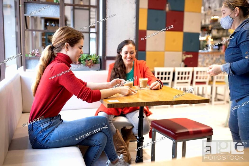 Imagen: Waitress looking at smiling female friends having coffee in cafe during COVID-19.
