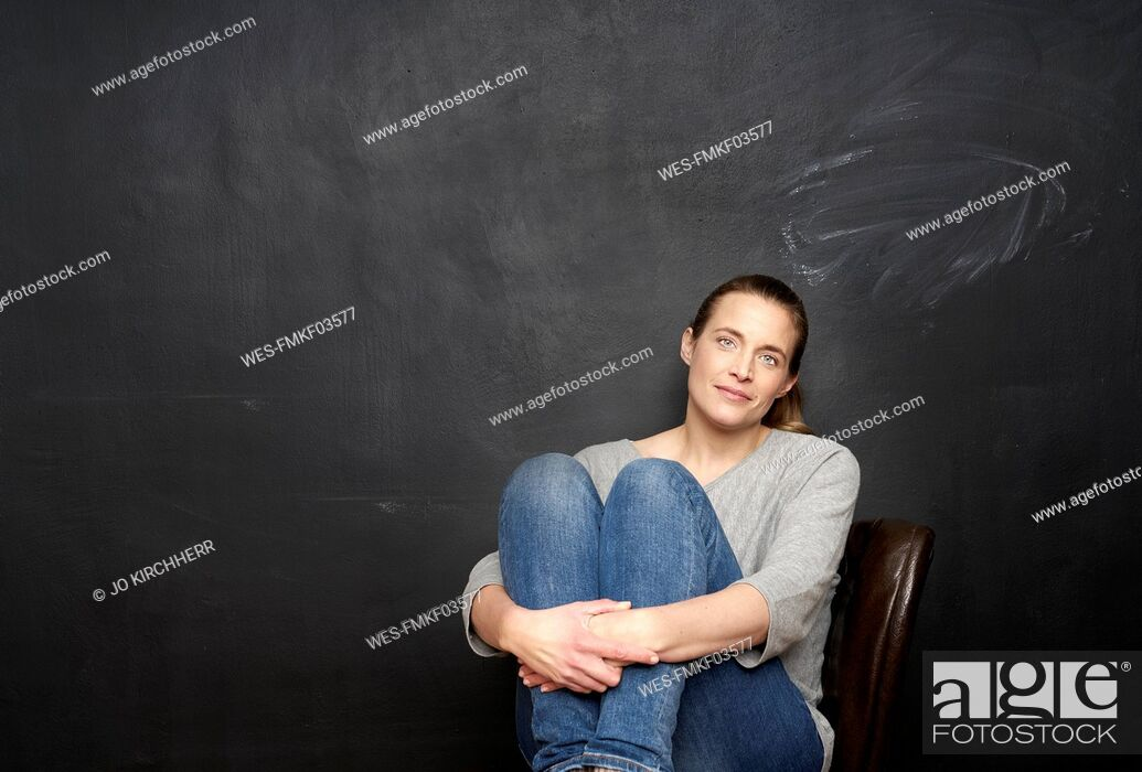 Stock Photo: Portrait of smiling woman sitting in front of blackboard.