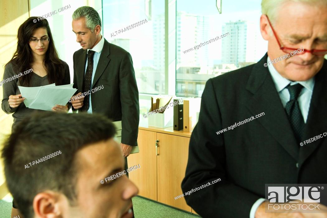 Stock Photo: Executives working with young associates in office.
