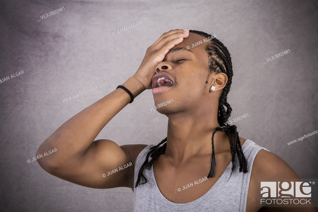 Stock Photo: Expressive young black man putting head to face on gray background.