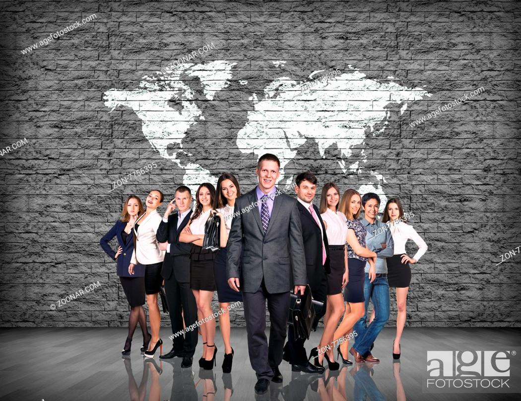 Imagen: businessmen team over gray brick wall with world map background. Elements of this image furnished by NASA.