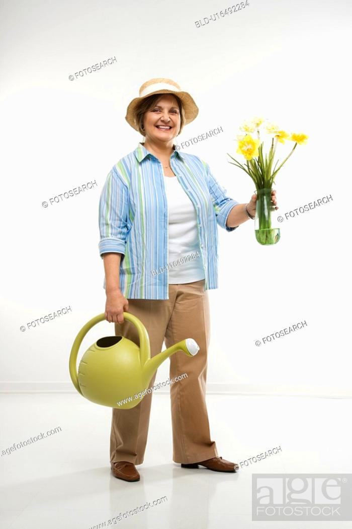 Stock Photo: Caucasian middle aged woman holding flowers and watering can.