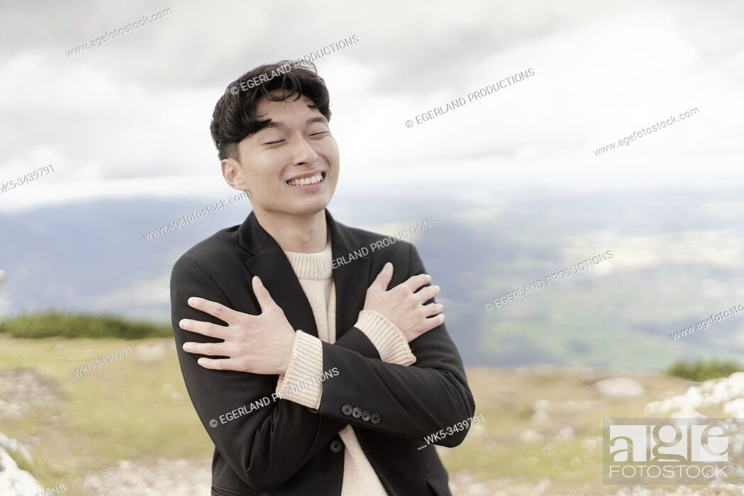 Stock Photo: smiling Korean man freezing on mountain in Europe, Austria, Salzburg, mount Untersberg.