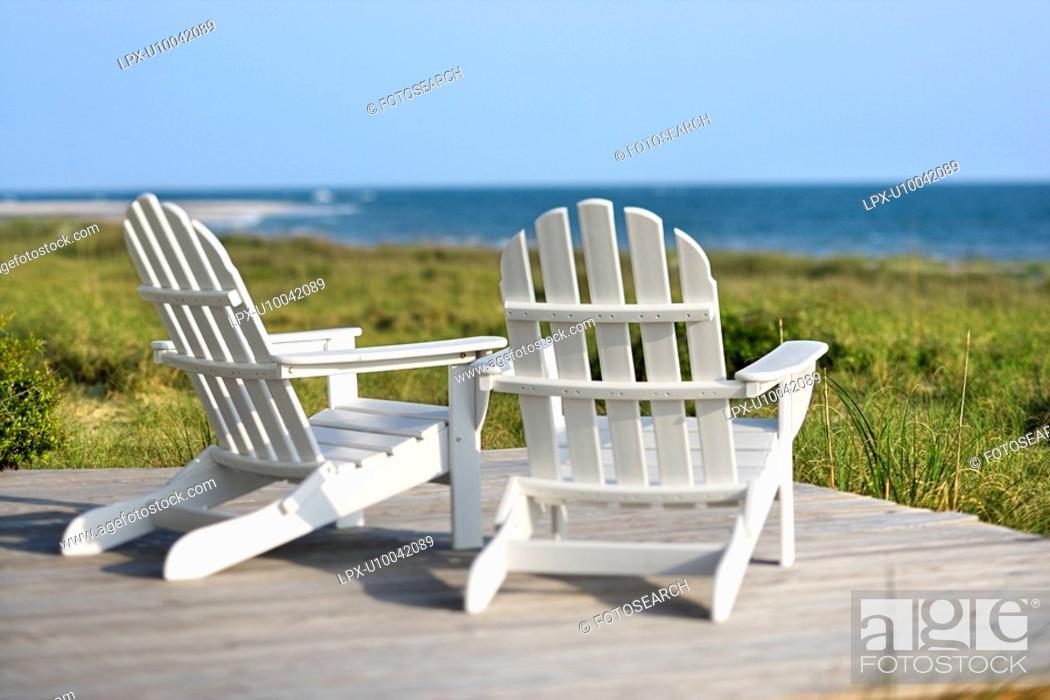 Stock Photo: Adirondack chairs on deck looking towards beach on Bald Head Island, North Carolina.