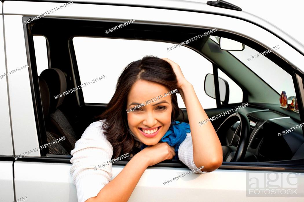 Stock Photo: Portrait of a woman sitting in a car and smiling.