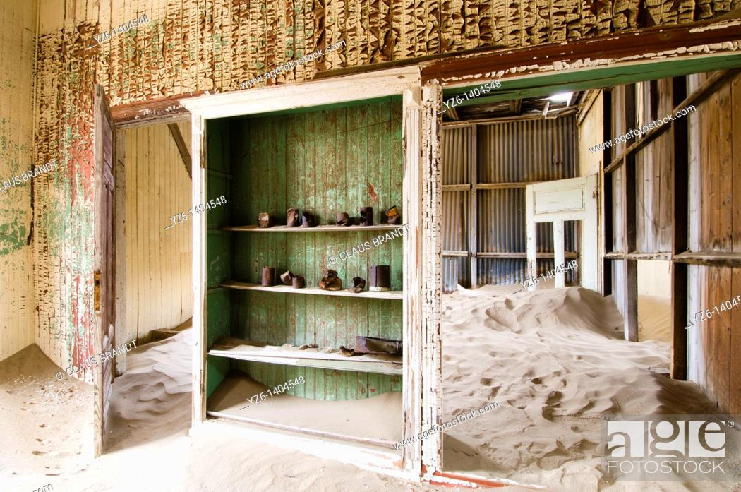 Stock Photo: Wooden cabinet with rusty tins in a room where sand has covered the floor. Ghost town of Kolmanskop, near Lüderitz, Namibia.
