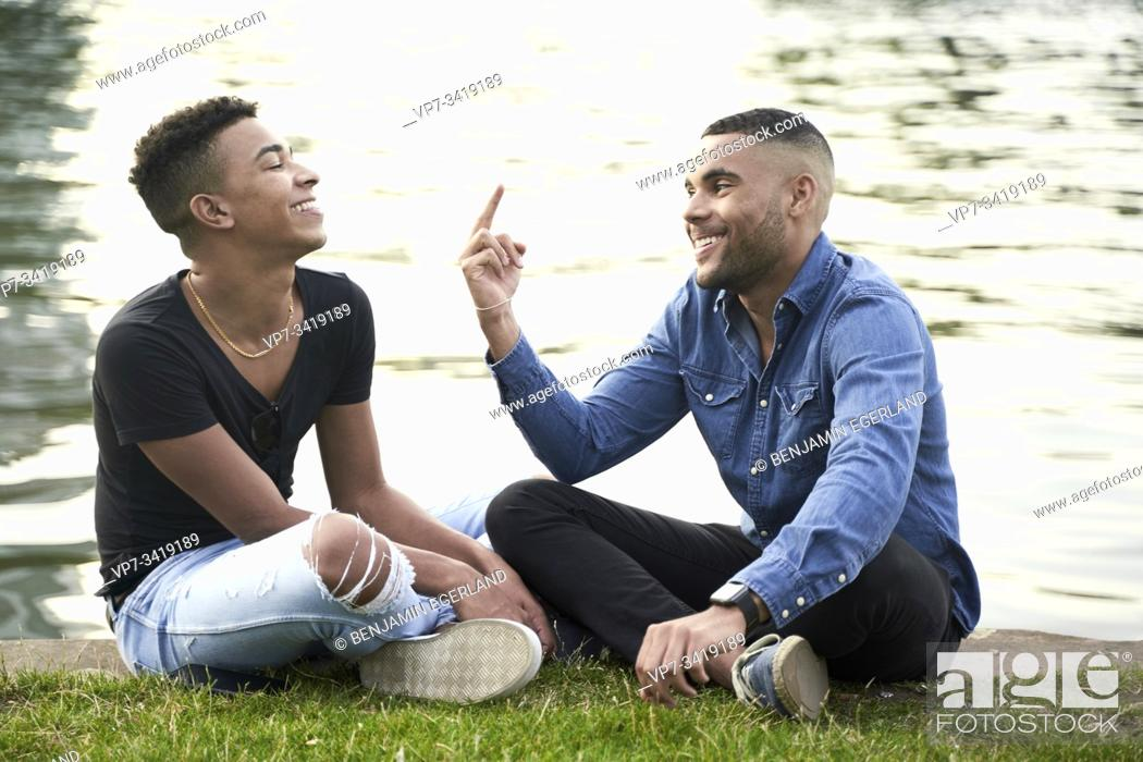 Imagen: Gay couple sitting on the grass. Frankfrut am Main, Germany.