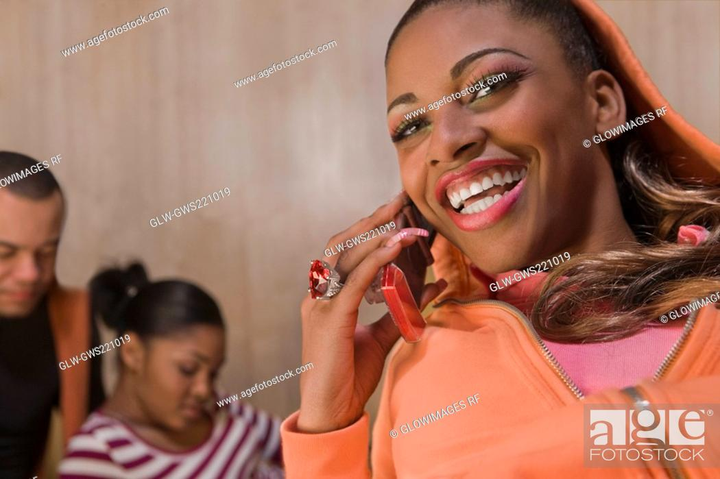 Stock Photo: Portrait of a young woman talking on a mobile phone and smiling.