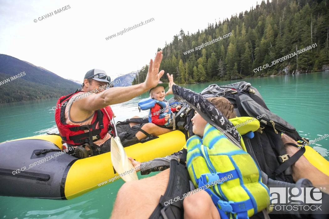 Photo de stock: Paddlers high-five during a father son paddling trip.