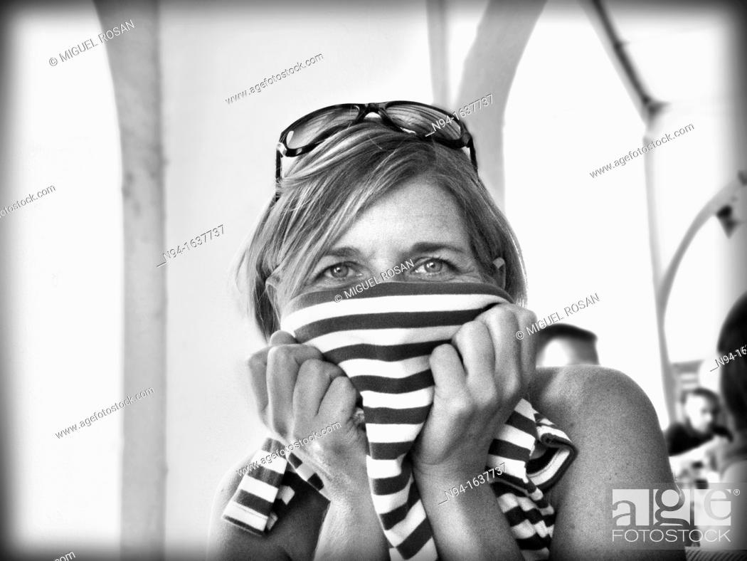 Stock Photo: Young blond woman with sunglasses on head, covering her face with a shirt.