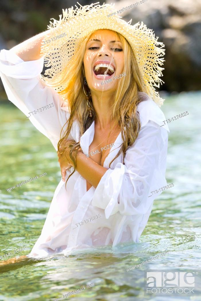 Stock Photo: Wet in men's shirt happy young woman in the water.